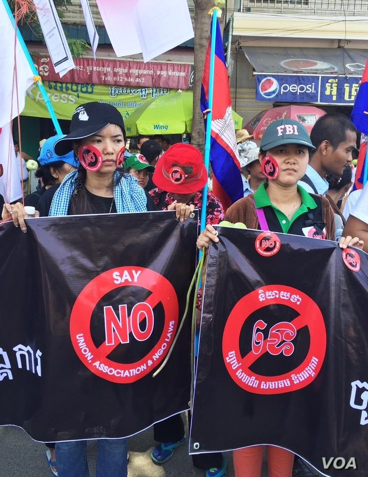 Two protesters against the controversial LANGO stand opposite the Cambodian Senate building as the bill is debated early Friday. (Robert Carmichael for VOA News)