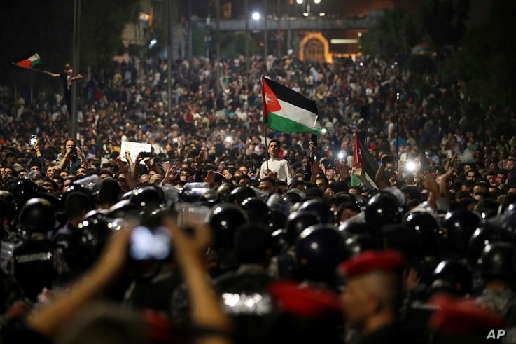 Jordanian protesters shout slogans and raise a national flag during a demonstration outside the Prime Minister's office in the capital Amman, June 4, 2018.