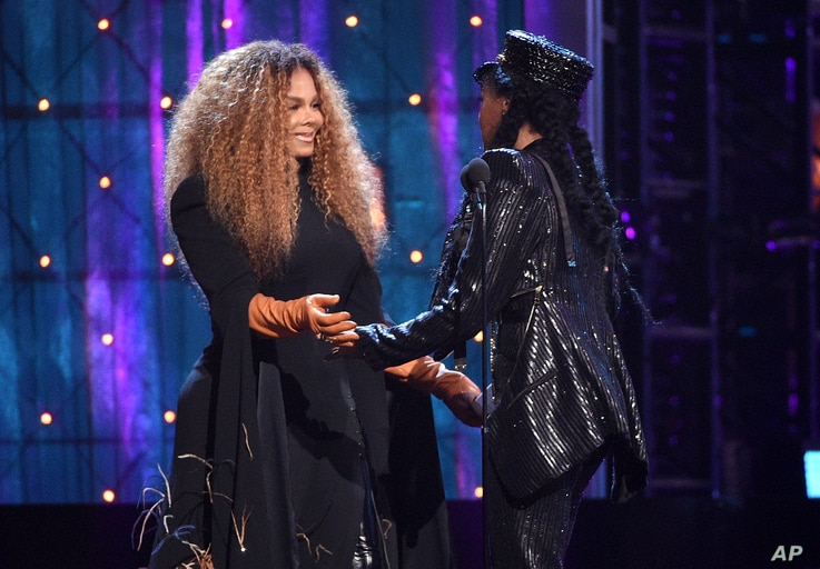Janelle Monae, right, presents a trophy to inductee Janet Jackson at the Rock and Roll Hall of Fame induction ceremony at the Barclays Center, March 29, 2019, in New York.
