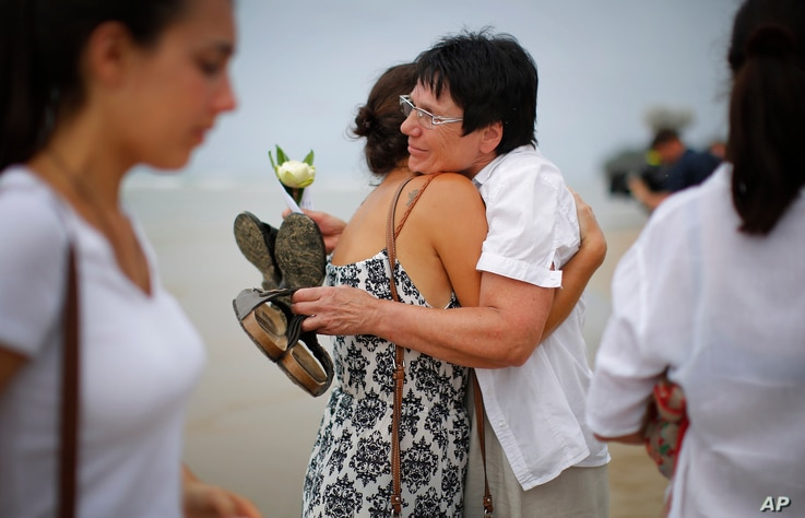Relatives of the Asian tsunami's victims comfort each other during a commemoration for Germans, Austrians and Swiss killed in Khao Lak, Thailand, Dec. 26, 2014.