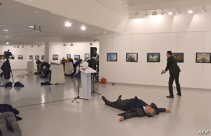 Andrey Karlov (2ndR), the Russian ambassador to Ankara, lying on the floor after being shot by a gunman (R) during an attack during a public event in Ankara, Turkey, Dec. 19, 2016.