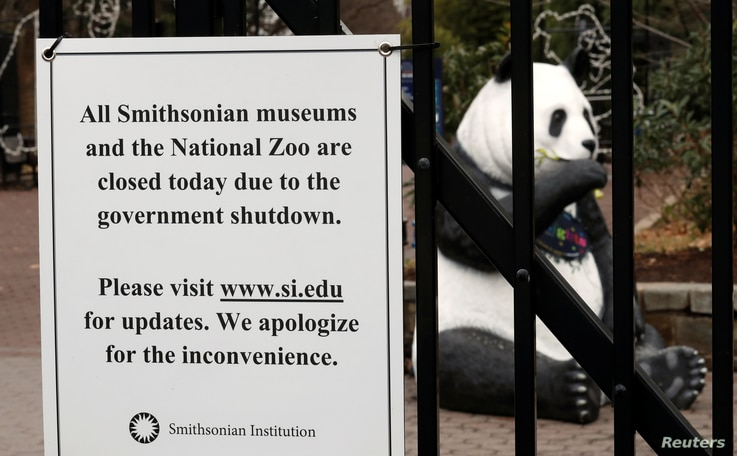 The figure of a panda is seen behind a sign telling the public that the National Zoo is closed due to the partial government shutdown in Washington, Jan. 2, 2019.