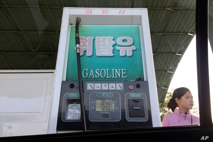 In this April 26, 2017, photo, a gas attendant waits by a pump at a gas station in Pyongyang, North Korea.