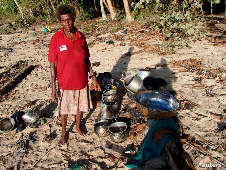A man collects his belongings after a tsunami hit Venga village on Solomon Islands, Feb. 7, 2013. (World Vision)