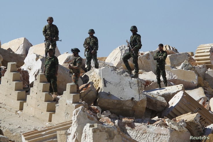 FILE - Syrian army soldiers stands on the ruins of the Temple of Bel in the historic city of Palmyra, in Homs Governorate, Syria, April 1, 2016.