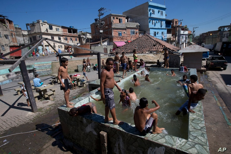 FILE - Children play in a pool that has no system to replace the water in Rio de Janeiro, Brazil, Aug. 13, 2015. Brazil is among the world's largest economies, but lags in access to water and sanitation. Rapid urban growth in recent decades, poor p...