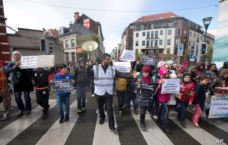 An organizer leads children holding signs out of the Molenbeek district during a march against hate in Brussels on Sunday, April 17, 2016.