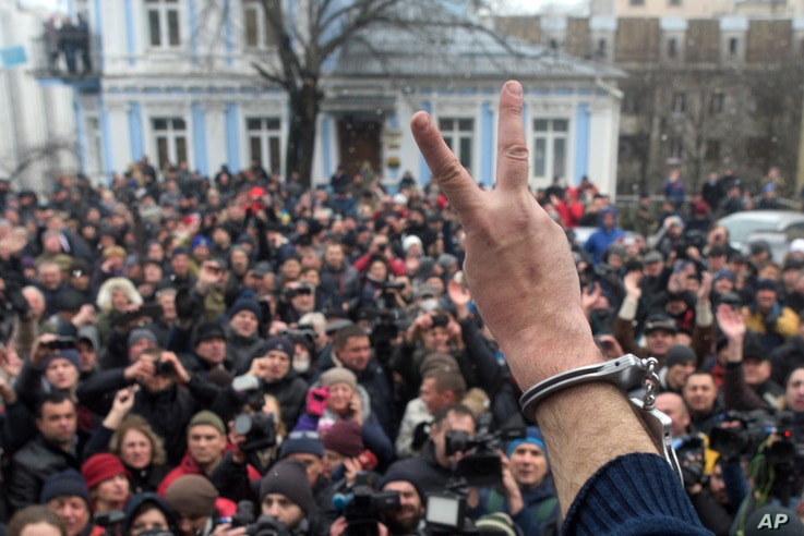 Former Georgian president Mikheil Saakashvili, back to a camera, gestures to protesters after he escaped with help from supporters and led them on a march toward parliament, where they planned to call for President Petro Poroshenko to resign in Kyiv,...