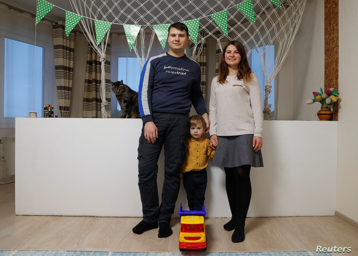 FILE - Alesia Rutsevich, 28, an ophthalmologist, her husband Pyotr, 28, a programmer, and their son Daniil, 3, pose for a photograph at their house in the week Alesia went back to work, in Minsk, Belarus, Feb. 23, 2019.