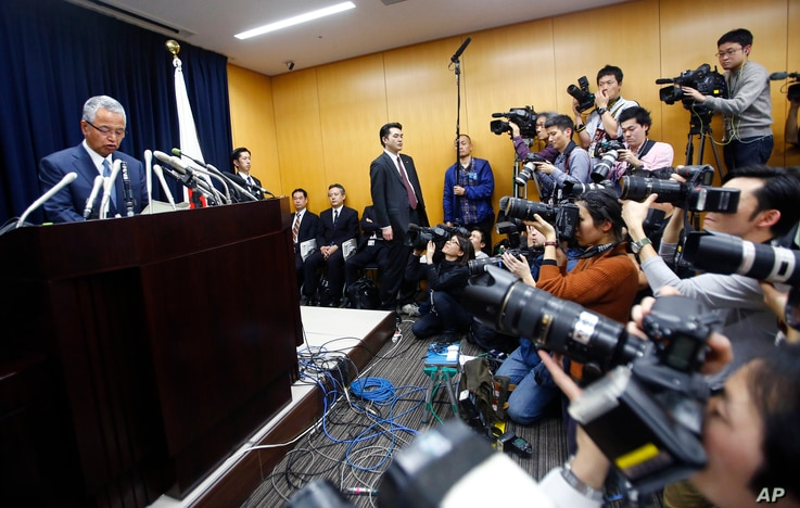 Japanese Economy Minister Akira Amari, left, speaks during a nationally televised news conference in Tokyo, an. 28, 2016.
