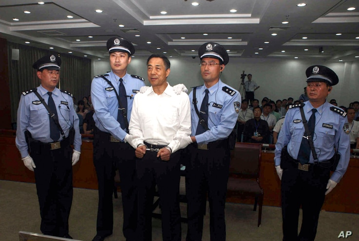 FILE - In this photo released by the Jinan Intermediate People's Court, fallen politician Bo Xilai, center, is handcuffed and held by police officers as he stands at the court in Jinan, in eastern China's Shandong province, Sept. 22, 2013.