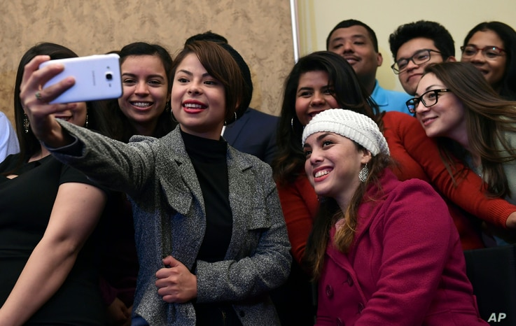 A group of Deferred Action for Childhood Arrivals program recipients take a selfie as they wait for the start of a news conference on Capitol Hill in Washington, Jan. 30, 2018, about legislation that will protect DACA recipients.