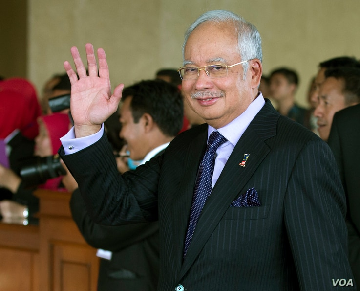 Malaysian Prime Minister Najib Razak waves as he arrives for the inauguration of Indonesia's seventh President Joko Widodo at Parliament in Jakarta, Indonesia, Oct. 20, 2014.