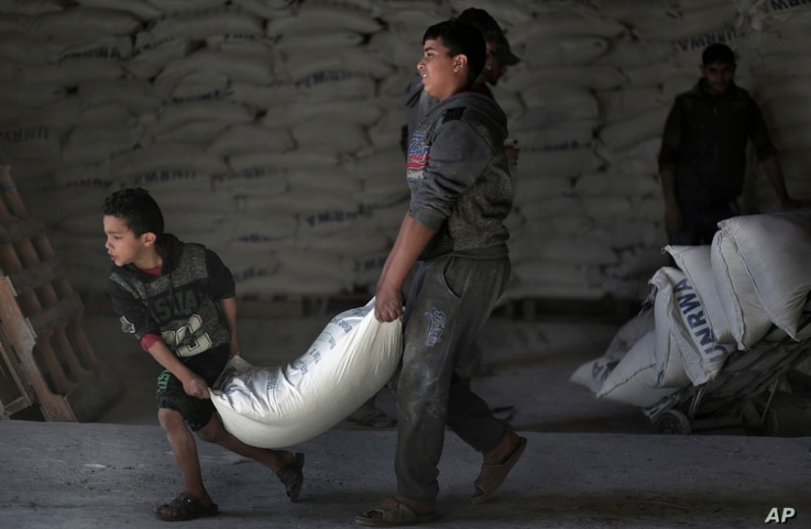 FILE - Palestinians receive UNRWA food aid at a U.N. warehouse at Shati refugee camp, in Gaza City, Jan. 14, 2018.