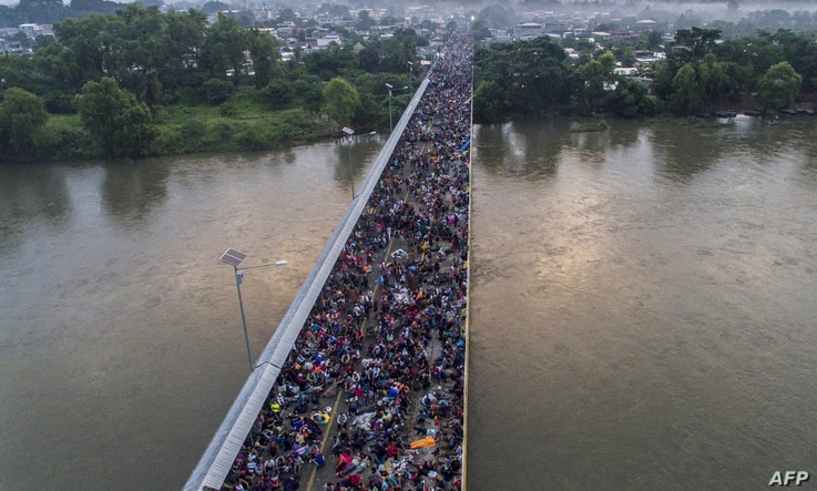 Aerial view of a Honduran migrant caravan heading to the US, on the Guatemala-Mexico international border bridge in Ciudad Hidalgo, Chiapas state, Mexico, Oct. 20, 2018.