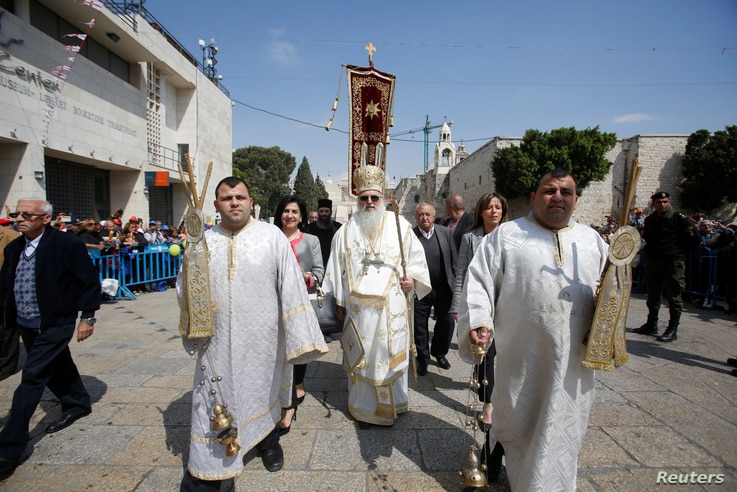 The head of the Greek Orthodox church in Bethlehem Bishop Theofilactos receives the 'Holy Fire' after its arrival from from Jerusalem's Holy Sepulchre, outside in the Church of the Nativity in the West Bank town of Bethlehem, April 15, 2017.