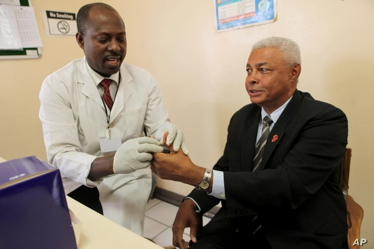 United States Ambassador to Zimbabwe, Charles A. Ray, right, takes an HIV test in Harare, December 1, 2010.