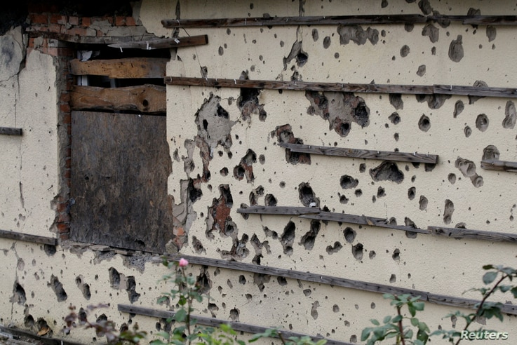The wall of a house covered in shrapnel scars is seen in Oktyabrsky district of Donetsk, Ukraine, Oct. 25, 2017.