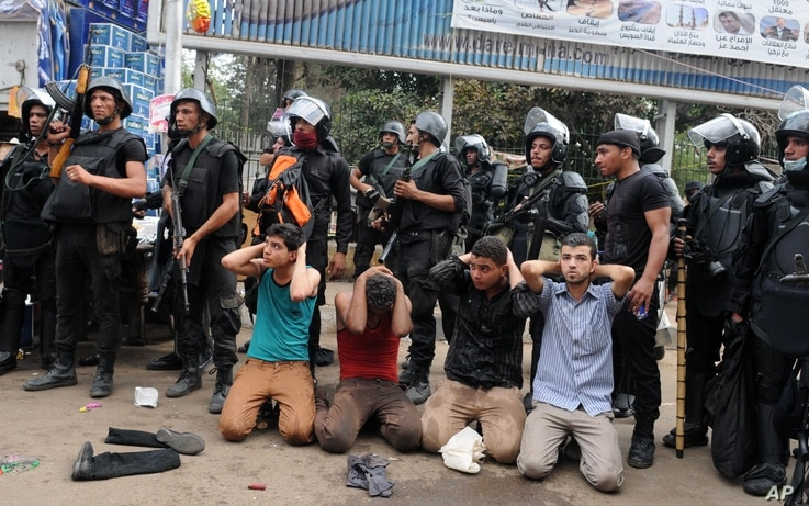 Egyptian security forces detain supporters of ousted President Mohamed Morsi as they clear a sit-in camp set up near Cairo University in Cairo's Giza district, Egypt, Aug. 14, 2013.