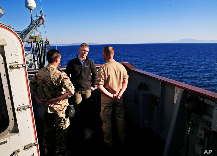 NATO Secretary General Jens Stoltenberg, center, talks with crew members of the NATO German warship FGS Bonn, on patrol in the Aegean Sea, off the Turkish coast, during a visit Thursday, April 21, 2016.