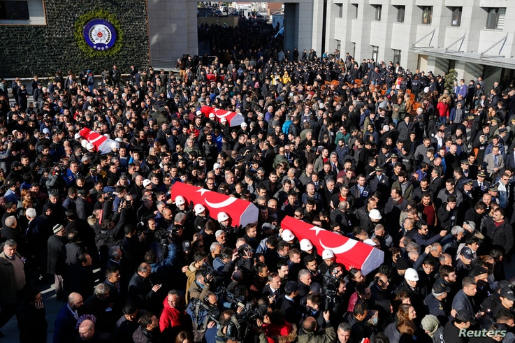 People carry the flag-draped coffins of police officers killed in Saturday's blasts in Istanbul, Dec. 11, 2016.