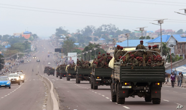 FILE - Congo military trucks carrying Congolese troops drive in a main street after violence erupted due to the delay of the presidential elections in Kinshasa, Democratic Republic of the Congo, Sept. 20, 2016.