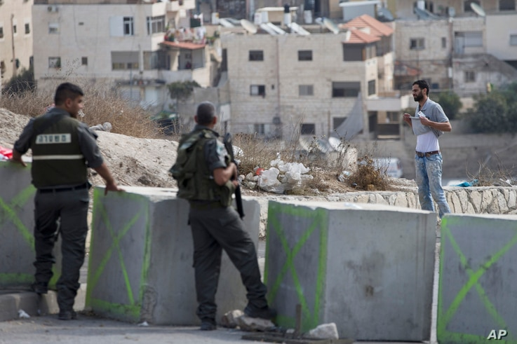 Israeli border police order a Palestinian man to lift his shirt at a checkpoint before he is allowed to exit the Arab neighborhood of Issawiyeh in Jerusalem, Oct. 20, 2015.