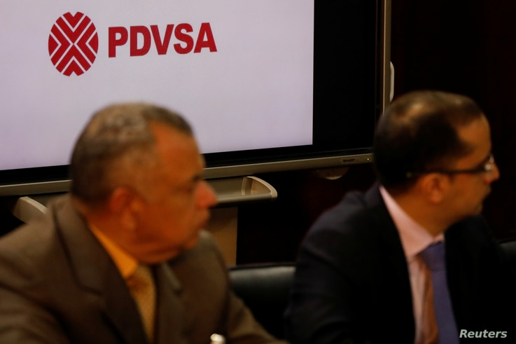 The corporate logo of the state oil company PDVSA is seen as Venezuela's Oil Minister and President of the Venezuelan state oil company PDVSA Manuel Quevedo talks to the media in Caracas, Venezuela, August 7, 2018.
