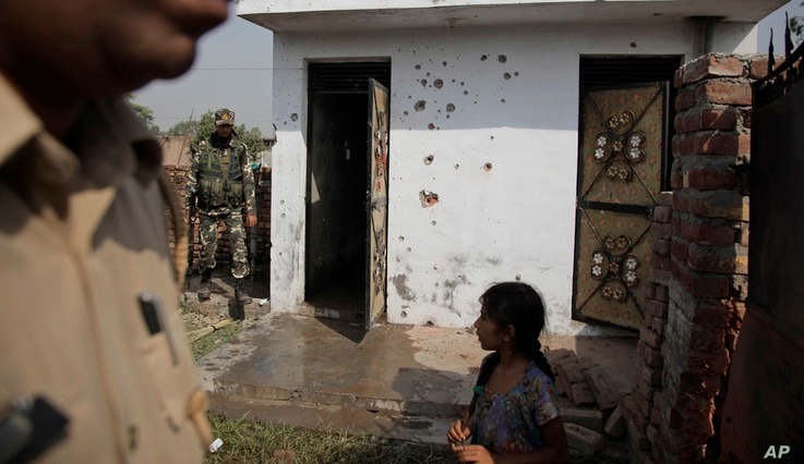 Indian security personnel inspect a house allegedly damaged by from gunfire from the Pakistan side of the border, at a residential area near the international border at Bidipur, in Ranbir Singh Pura, India, Oct. 22, 2016.