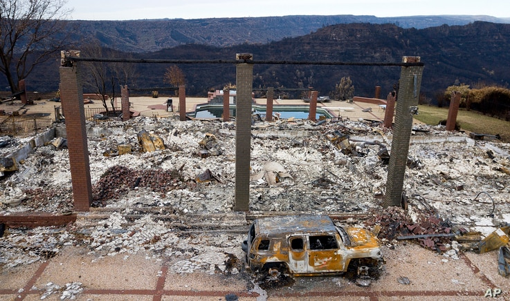 FILE - A vehicle rests in front of a home leveled by the Camp Fire in Paradise, Calif., Dec. 3, 2018. Authorities estimate it will cost at least $3 billion to clear debris of 19,000 homes destroyed by California wildfires last month.
