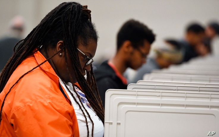 People stand cast their ballots ahead of the Nov. 6, general election at Jim Miller Park, Oct. 27, 2018, in Marietta, Ga.