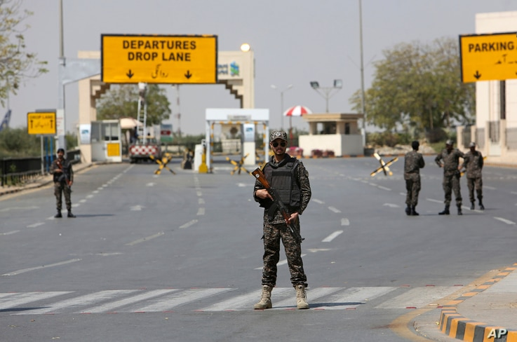 Pakistani troops stand guard on a blocked road to the Jinnah International Airport in Karachi, Feb. 28, 2019.