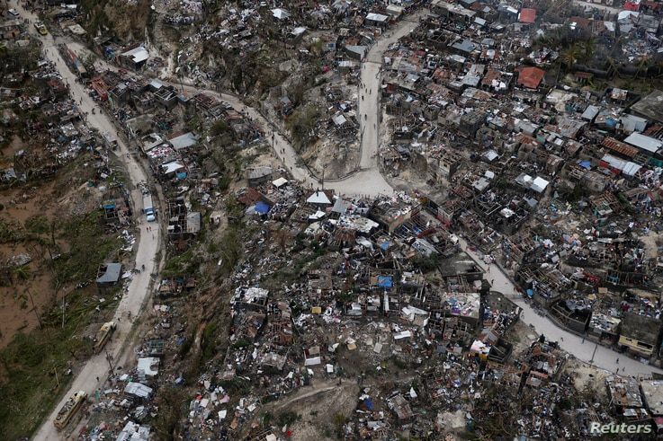 People walk down the streets next to destroyed houses after Hurricane Matthew passes Jeremie, Haiti, Oct. 5, 2016.