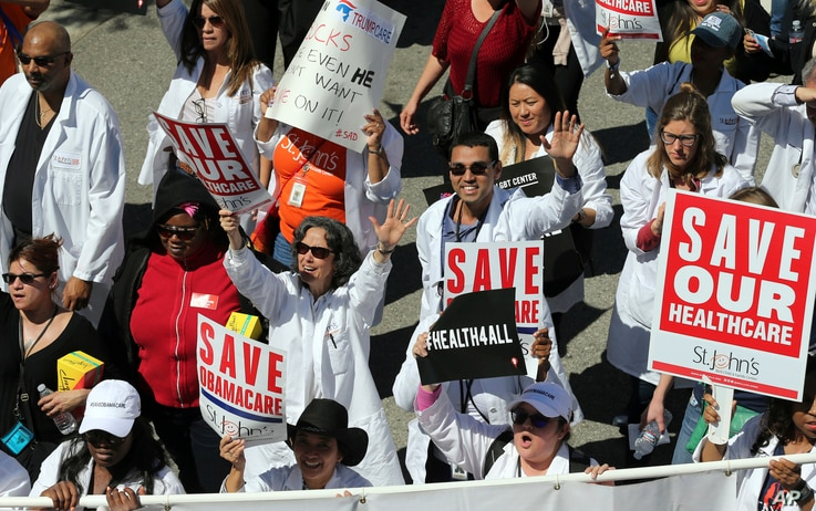 Health care professionals join hundreds of people march through downtown Los Angeles protesting President Donald Trump's plan to dismantle the Affordable Care Act, his predecessor's signature health care law, March 23, 2017.