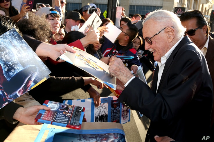"""Comic-book writer Stan Lee signs autographs as he arrives at the Los Angeles premiere of """"Captain America: Civil War"""" at the Dolby Theatre, April 12, 2016."""