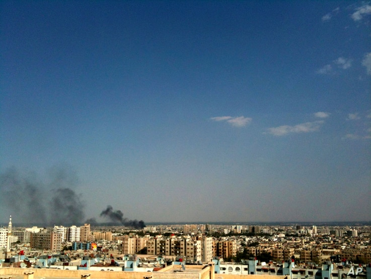 FILE - Smoke rises over the skyline in the Qaboun neighborhood of Damascus, Syria, July 19, 2012, during shelling by Syrian government forces.