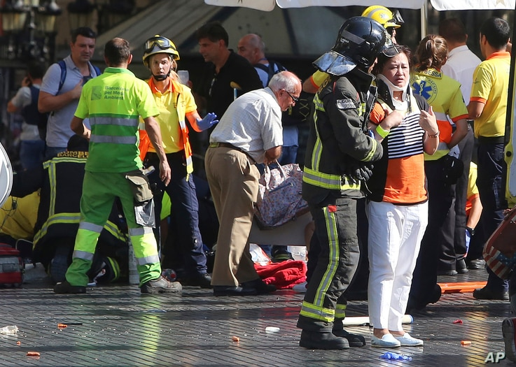 Injured people are treated in Barcelona, Spain, Aug. 17, 2017 after a van jumped the sidewalk in the historic Las Ramblas district, crashing into a summer crowd of residents and tourists.