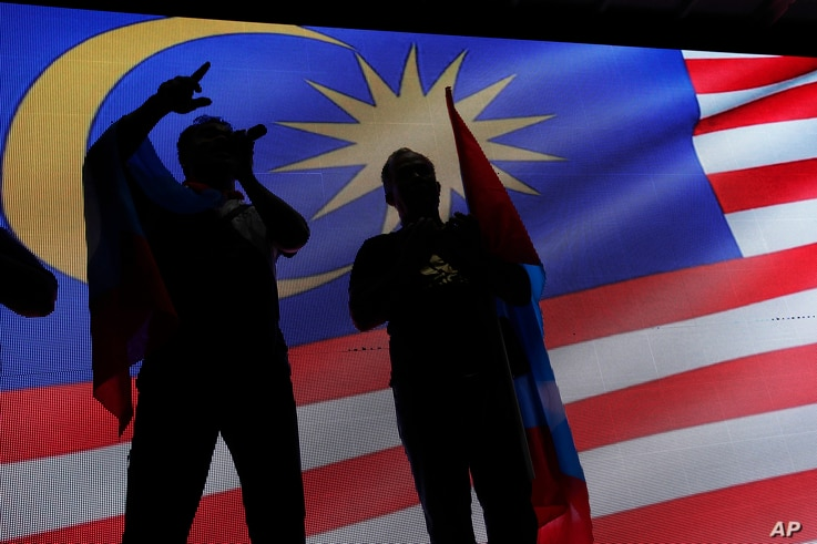 Opposition party supporters display a Malaysia national flag after Mahathir Mohamad claims the opposition party wins the General Election, broadcast on a large screen at a field in Kuala Lumpur, Malaysia, May 9, 2018.