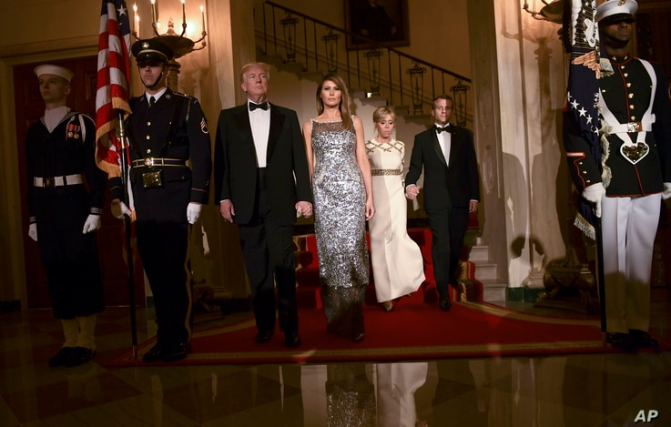 President Donald Trump, first lady Melania Trump, Brigitte Macron, and French President Emmanuel Macron walk down the Grand Staircase to pose for a photo in Grand Foyer before a State Dinner at the White House in Washington, April 24, 2018.