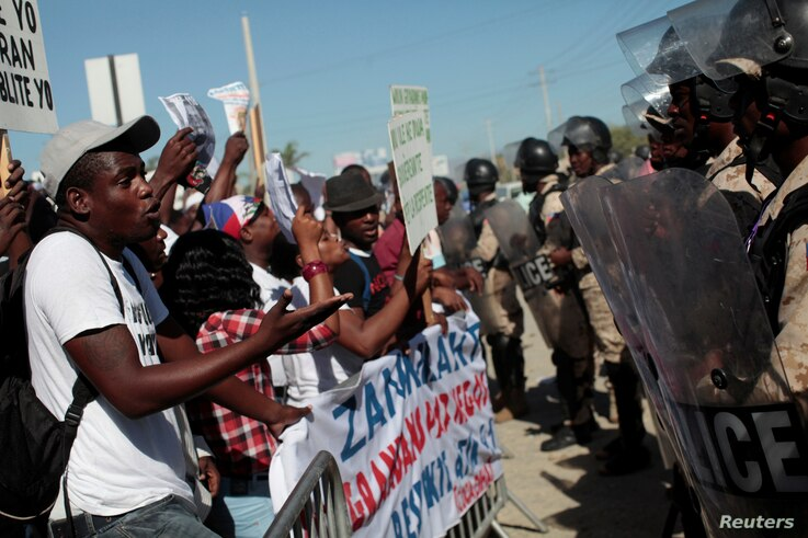 A supporter of Haitian Senator-elect Guy Philippe, who was arrested and extradited to the U.S., speaks to a police officer during a protest in front of the U.S. embassy in Port-au-Prince, Jan. 13, 2017.