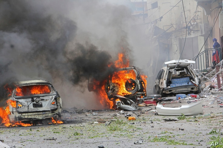 Burning vehicles are seen outside Midnimo mall after a car bomb attack on a popular mall in Mogadishu, Somalia, July 30, 2017.