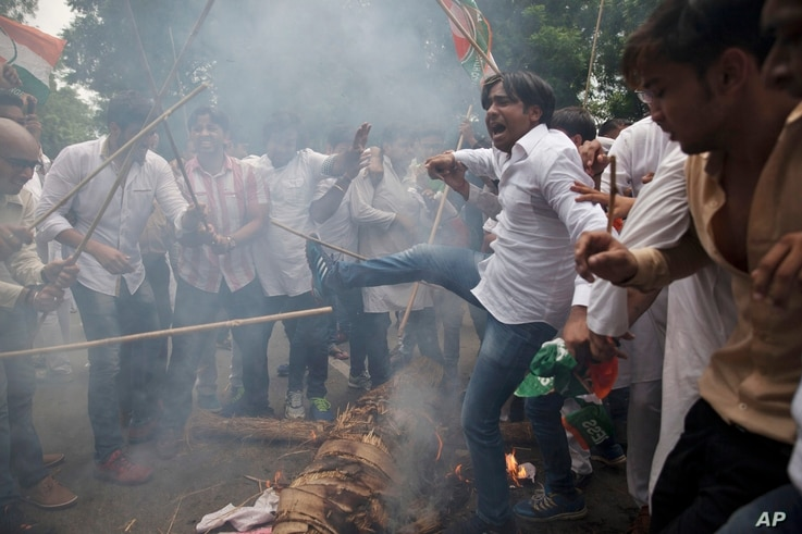 Activists of India's opposition Congress party's youth wing protesting against Monday's rebel attack in Punjab state burn an effigy representing Prime Minister Narendra Modi and Punjab state Chief Minister Parkash Singh Badal in New Delhi, India, J...