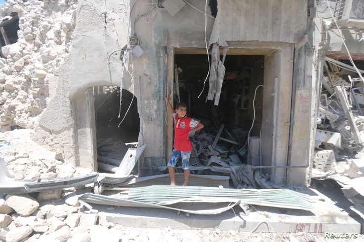 A boy stands at a site hit by a barrel bomb in the rebel-held area of Old Aleppo, Syria, July 11, 2016.