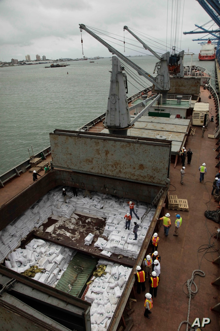 Panamanian workers stand atop sacks of sugar inside a container aboard a North Korean-flagged ship at the Manzanillo International container terminal on the coast of Colon City, Panama, Tuesday, July 16, 2013. The North Korean ship carrying weapons s...