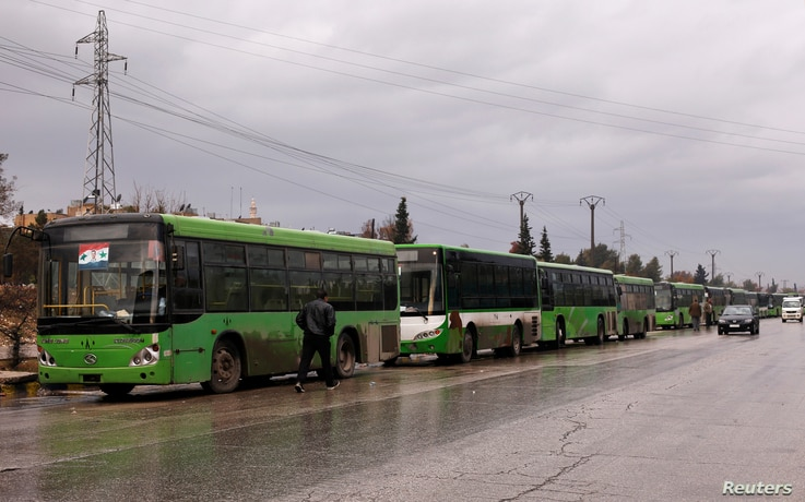 Buses wait to evacuate people from a rebel pocket in Aleppo, in the government-controlled al-Hamadaniah Stadium of Aleppo, Syria Dec. 14, 2016.