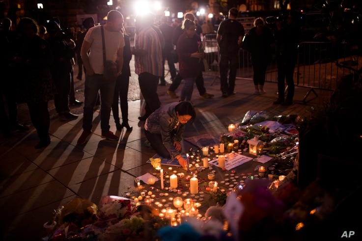 A woman lights candles after a vigil in Albert Square, Manchester, England, May 23, 2017.
