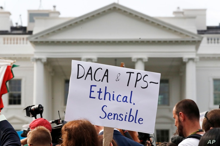 FILE - A person holds up a sign in support of the Deferred Action for Childhood Arrivals, known as DACA, and Temporary Protected Status programs during a rally in support of DACA and TPS outside of the White House, in Washington.