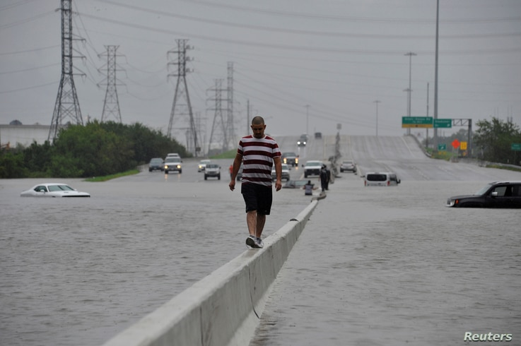 A stranded motorist escapes floodwaters on Interstate 225 after Hurricane Harvey inundated the Texas Gulf coast with rain causing mass flooding, in Houston, Texas, U.S. August 27, 2017.