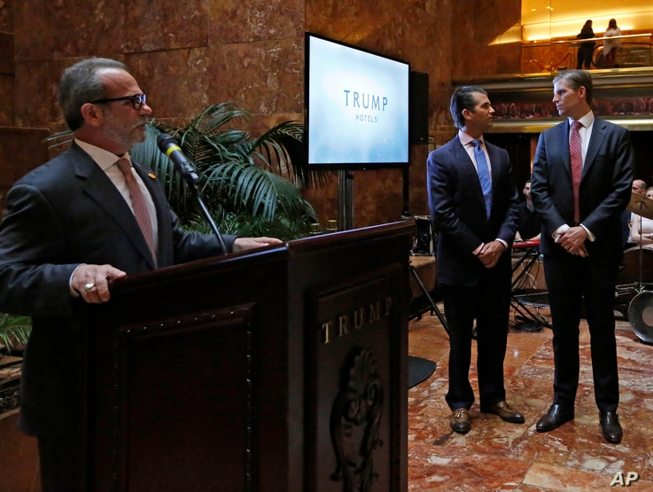 """Trump Hotels CEO Eric Danziger, left, speaks as Donald Trump Jr., center, and Eric Trump glance around the room during an event, June 5, 2017, at Trump Tower in New York. The Trump Organization is launching a new mid-market hotel chain called """"Americ..."""