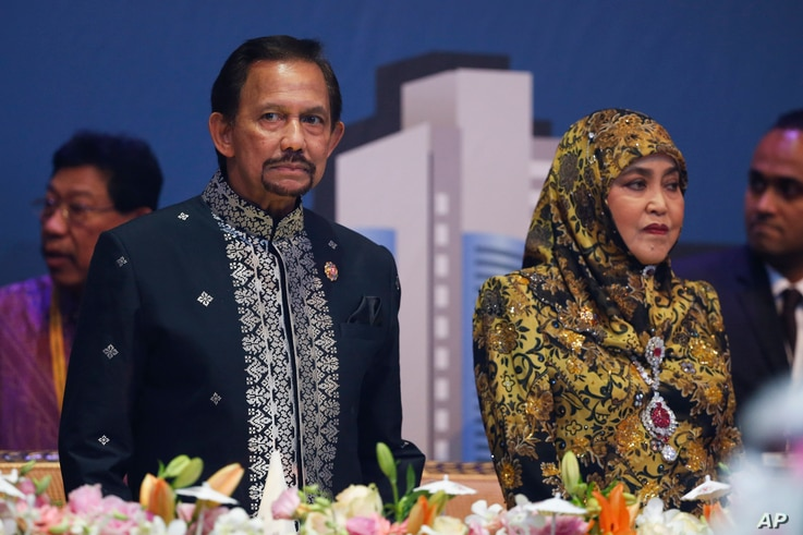 FILE - Brunei Sultan Hassanal Bolkiah, left, and wife Queen Saleha attends the Gala Dinner at the 27th ASEAN Summit in Kuala Lumpur, Malaysia. The conservative ruler has banned all Christmas celebrations in Islamic Brunei.